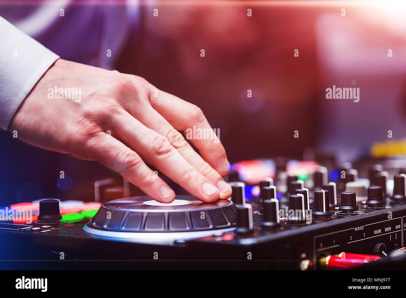 Disk jockey playing music at dj controller - Stock Image