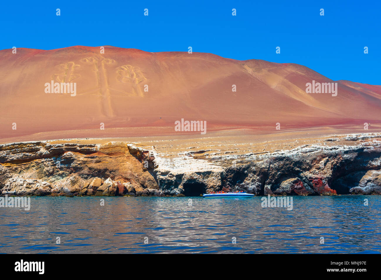 Paracas, Peru -- April 11, 2018. A tour boat hovers near desert caves on the coast of the Paracas Desert.  The famous Nazca lines are replicated on a  - Stock Image