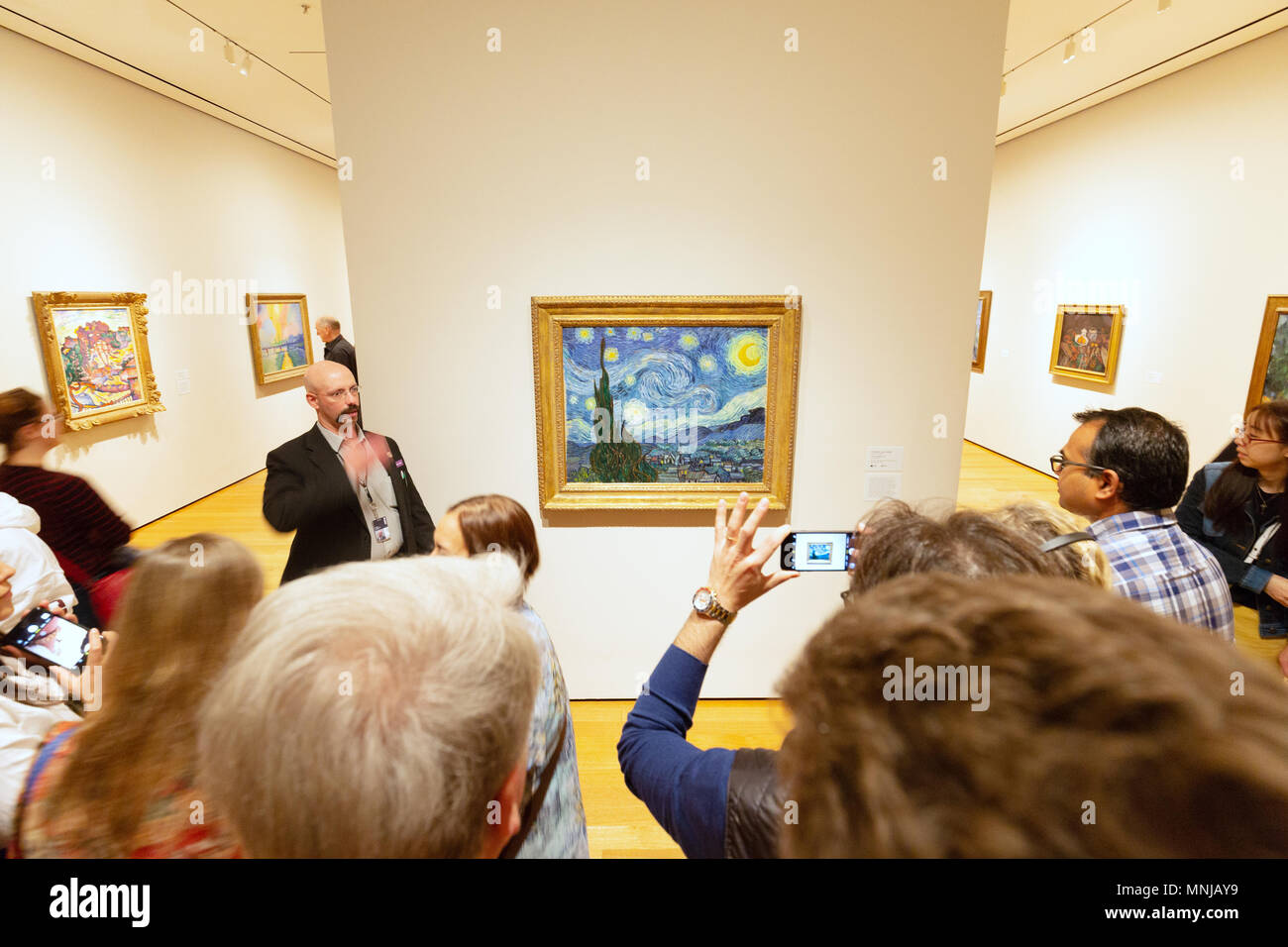 MoMA - Museum of Modern Art New York interior - people looking at ' The Starry Night ' oil painting by Vincent Van Gogh, MoMA, New York city USA - Stock Image