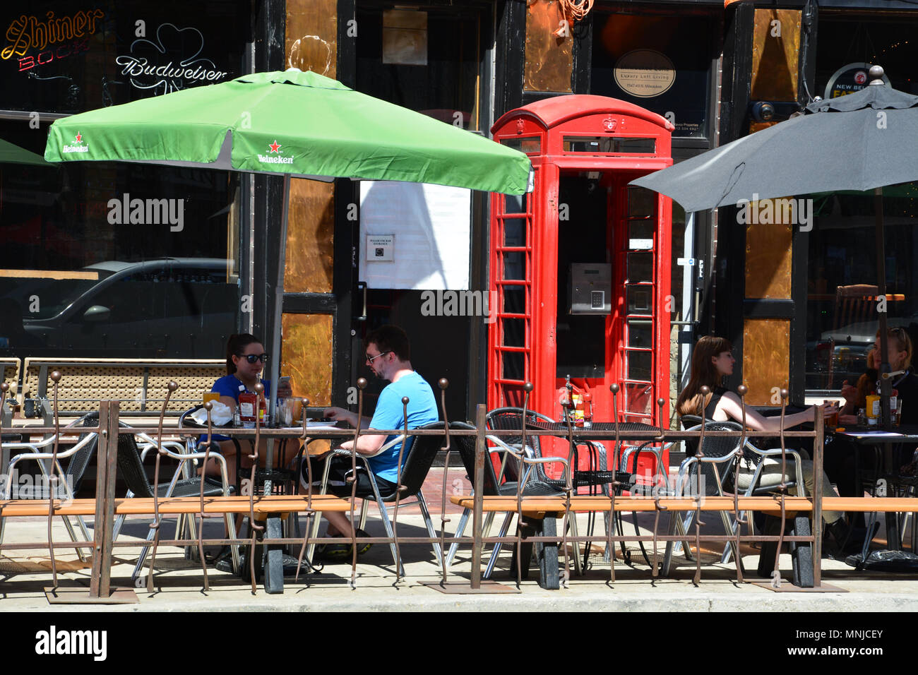 Patrons drink at a sidewalk cafe in the trendy Wicker Park neighborhood of Chicago. - Stock Image
