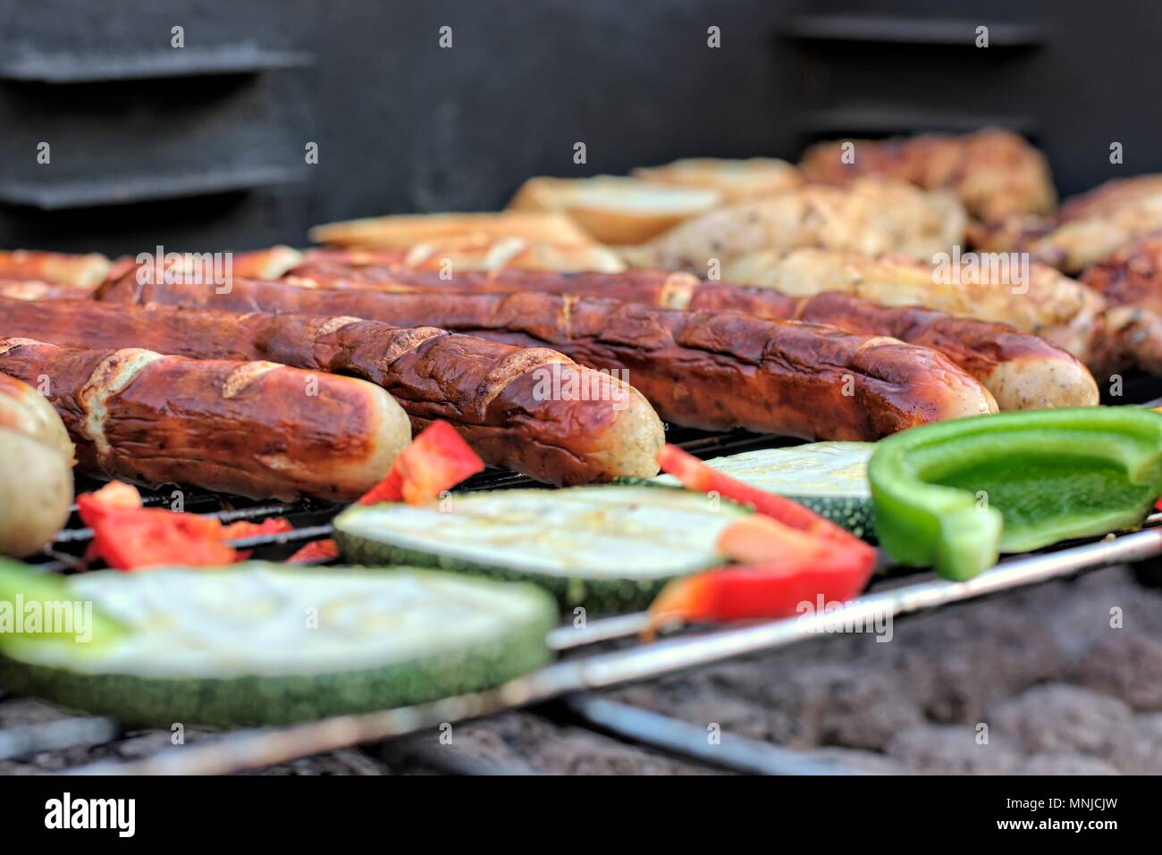Tasty food, nutrition, culinary and barbecue concept: grilled sausages,chicken thigh and vegetables on a barbeque. - Stock Image