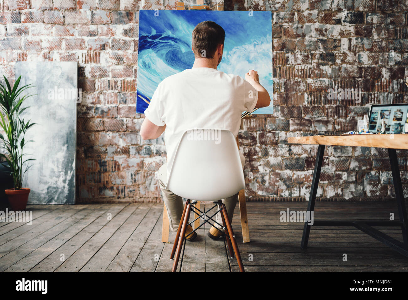 Professional painter sits on chair in front of easel with canvas, hold paintbrush in hand and drawing oil painting. Artist working process in studio.  Stock Photo