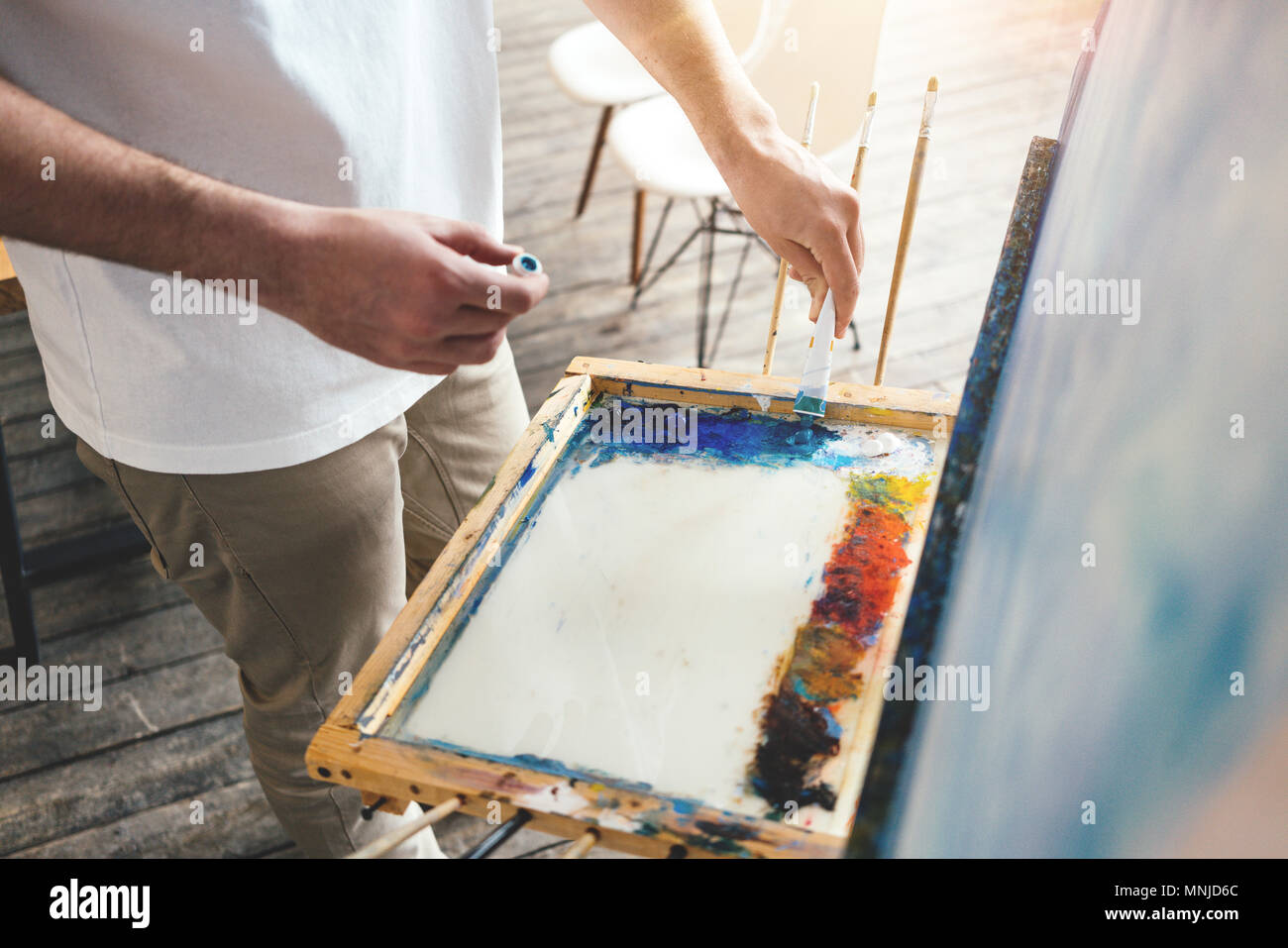 Painter mixes oil paint colors on the palette in workshop. Men artist in light studio. Lens flare effect - Stock Image