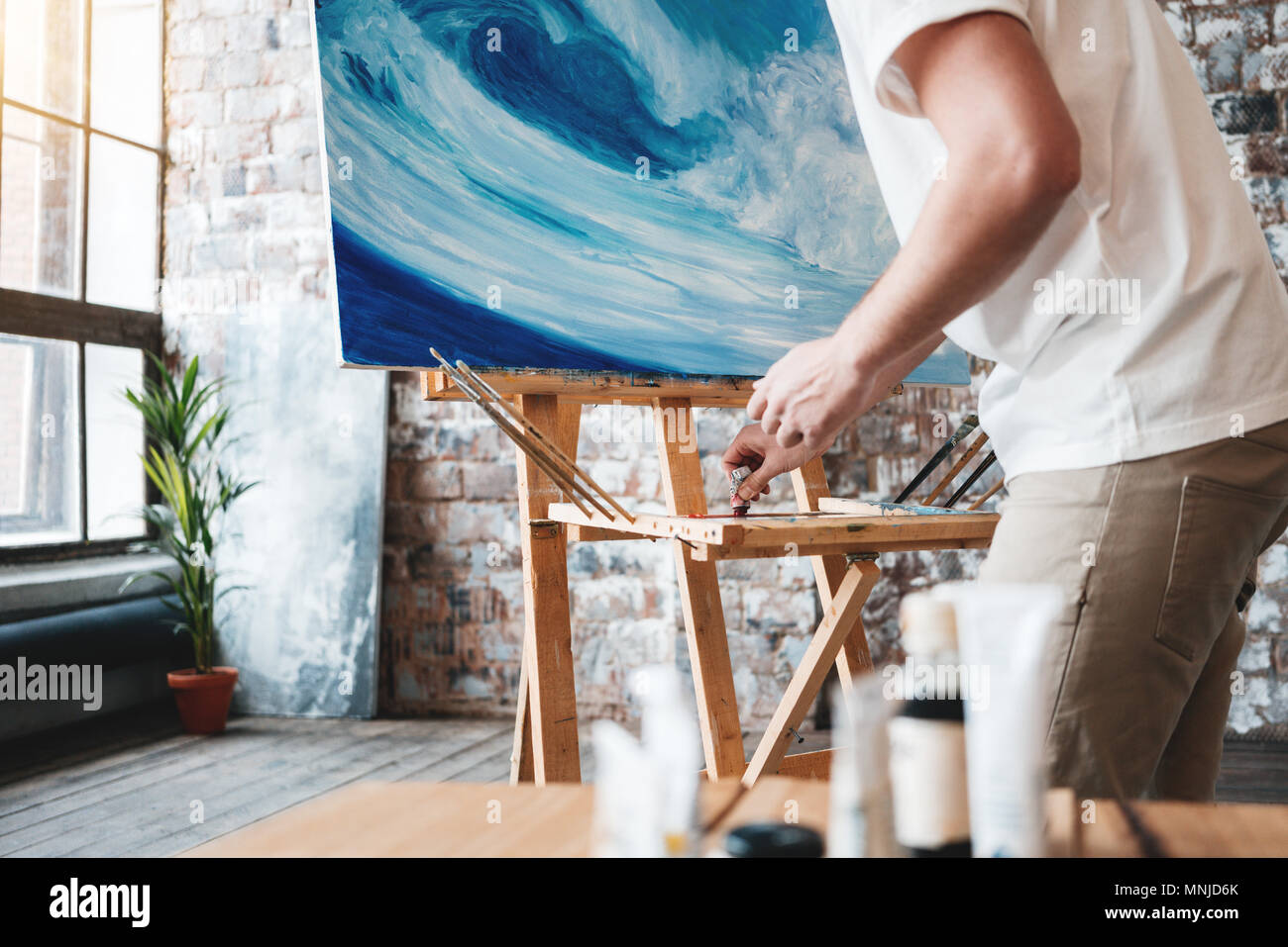 Artist work in art studio near easel with canvas. Painter paints a painting with oil paints in loft studio. Drawing workshop. Creative class - Stock Image