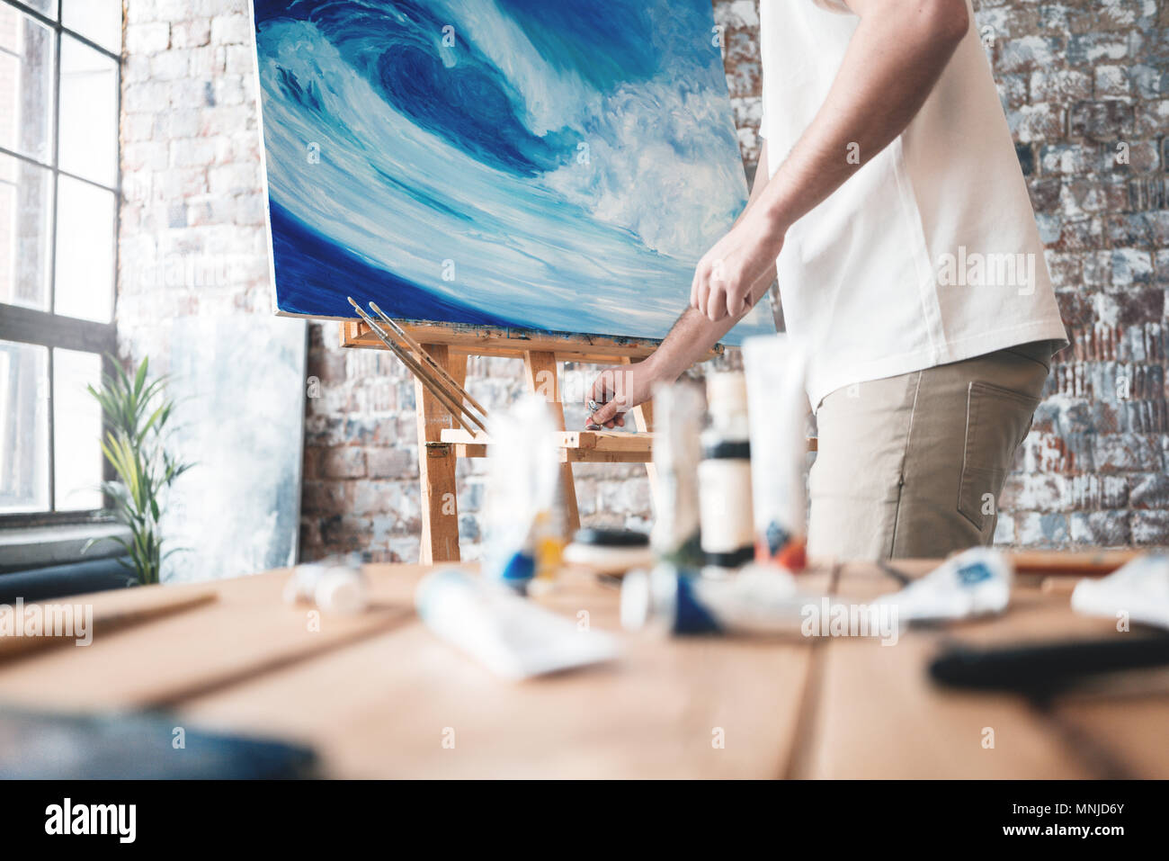 Painter artwork at workspace. Professional male artist painting on canvas in studio - Stock Image