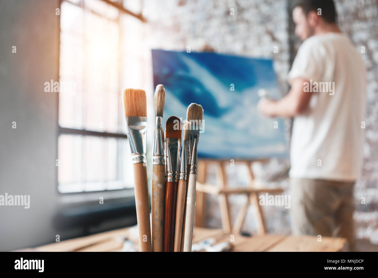 Different artist paintbrushes clouseup on background of painter near canvas on the easel. Drawing workshop. Creative classe. Flare effect - Stock Image