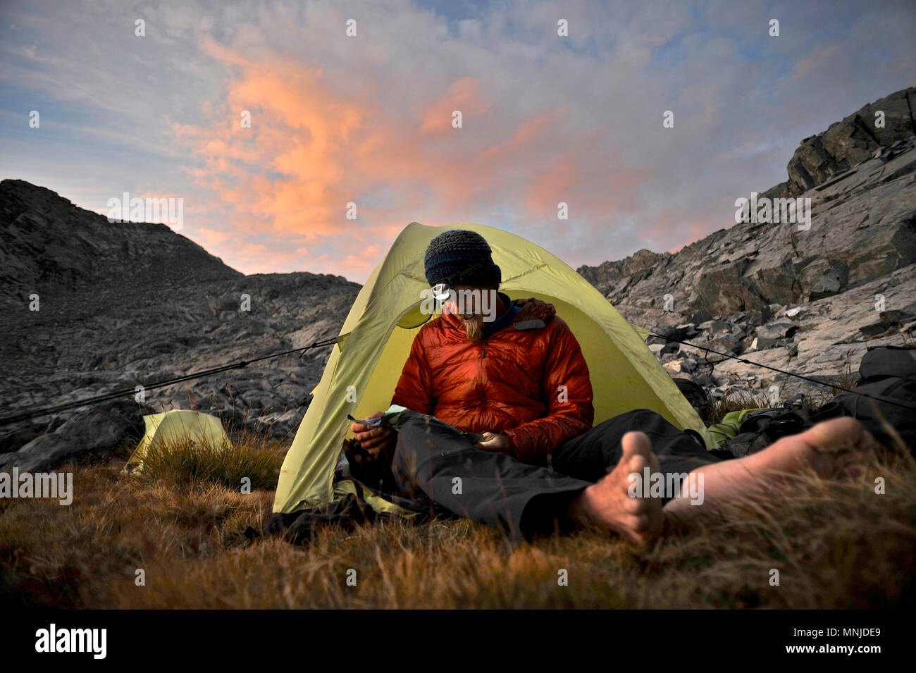 Backpackers use headlamps at camp near Mt Ritter while on trek of Sierra High Route in Minarets Wilderness, Inyo National Forest, California, USA - Stock Image