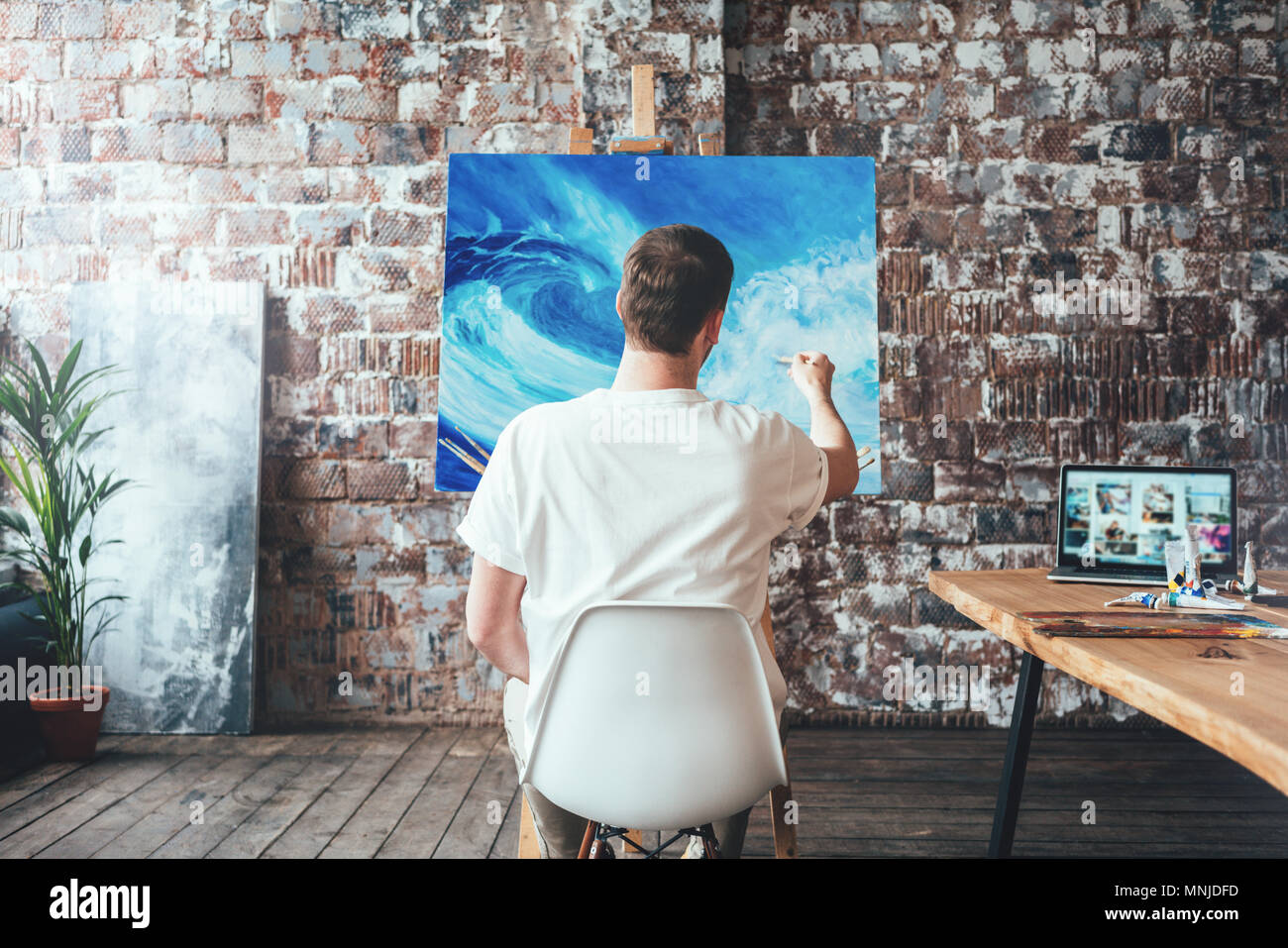 Man artist sitting on chair in front of canvas on easel and drawing. Painter working in workshop - Stock Image