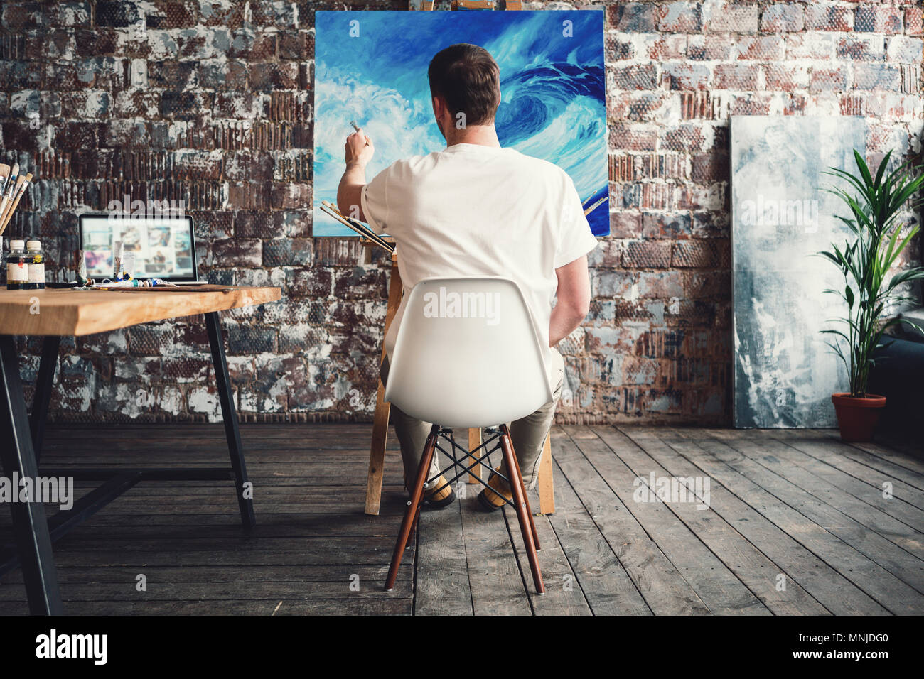 Artist in art studio sits on chair in front of canvas on easel and drawing. Painter work in workshop. Working process. Hobby concept Stock Photo