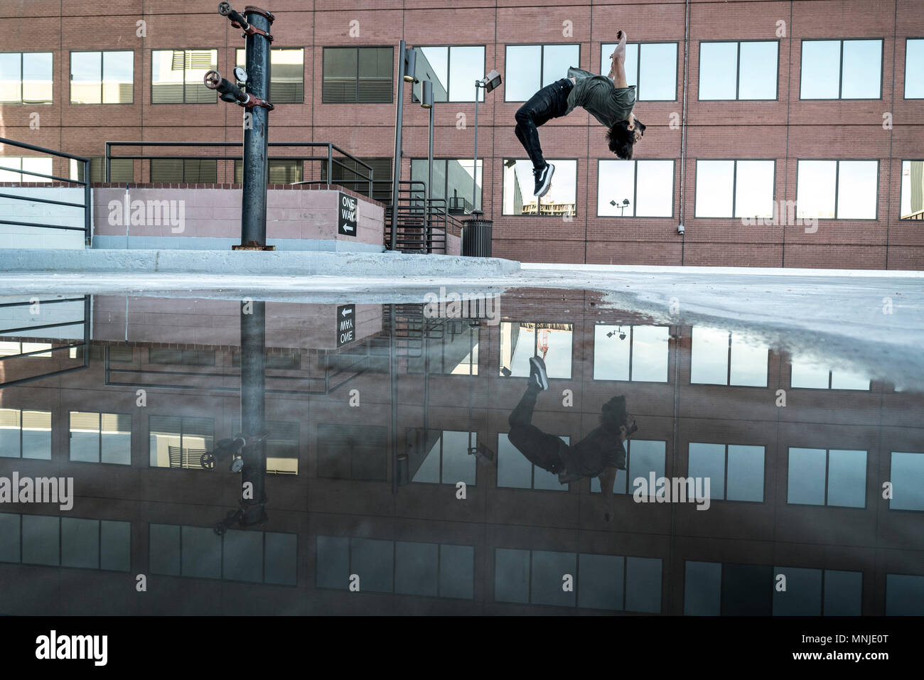 Park athlete in mid back flip in parking lot in downtown Denver, Colorado, USA - Stock Image