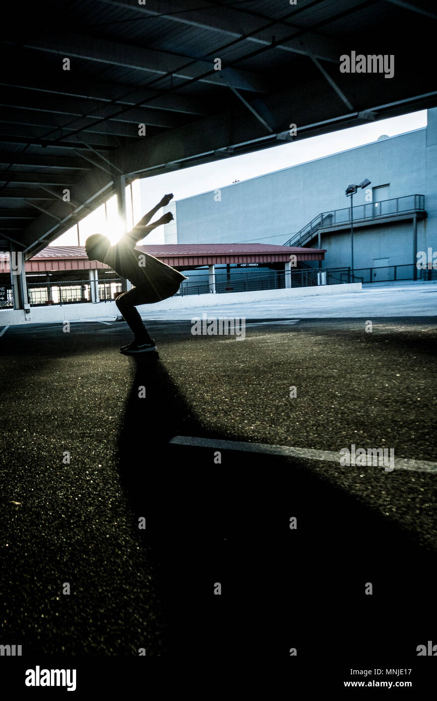 Park athlete gears up to do standing back flip in parking lot in downtown Denver, Colorado - Stock Image