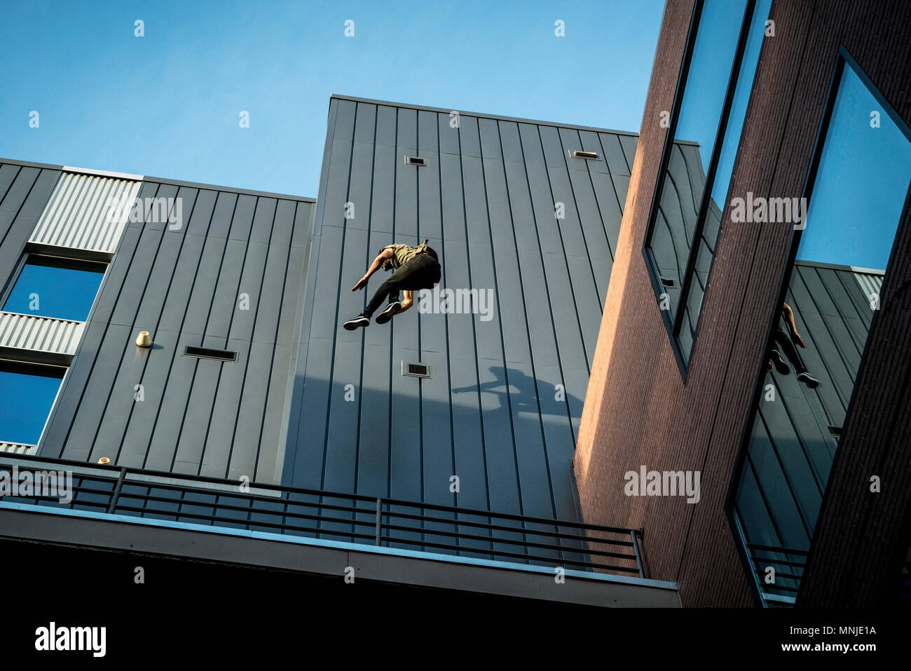 Male park athlete jumping from one roof to another in downtown Denver, Colorado, USA - Stock Image