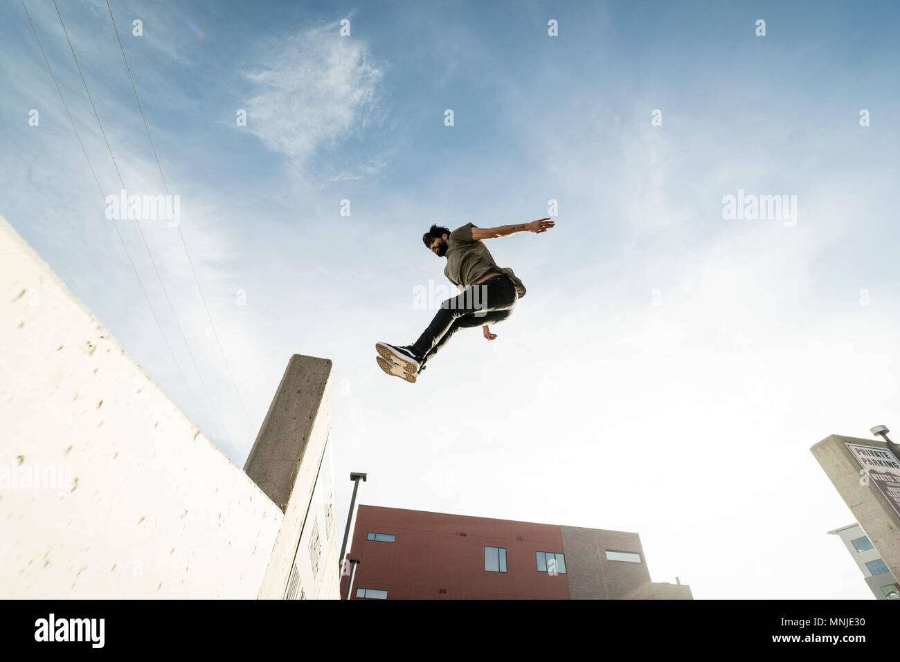 Park athlete jumping into ledge in downtown Denver, Colorado, USA - Stock Image