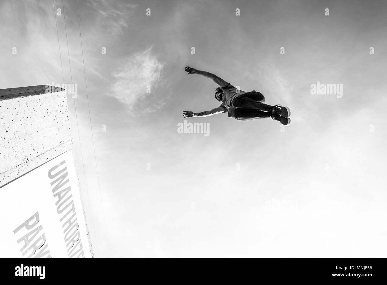 Park athlete jumping high gap in parking lot in downtown Denver, Colorado, USA - Stock Image