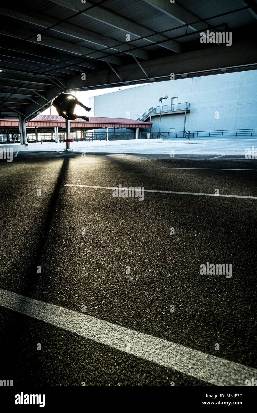 Park athlete doing side flip in parking lot in downtown Denver, Colorado, USA - Stock Image