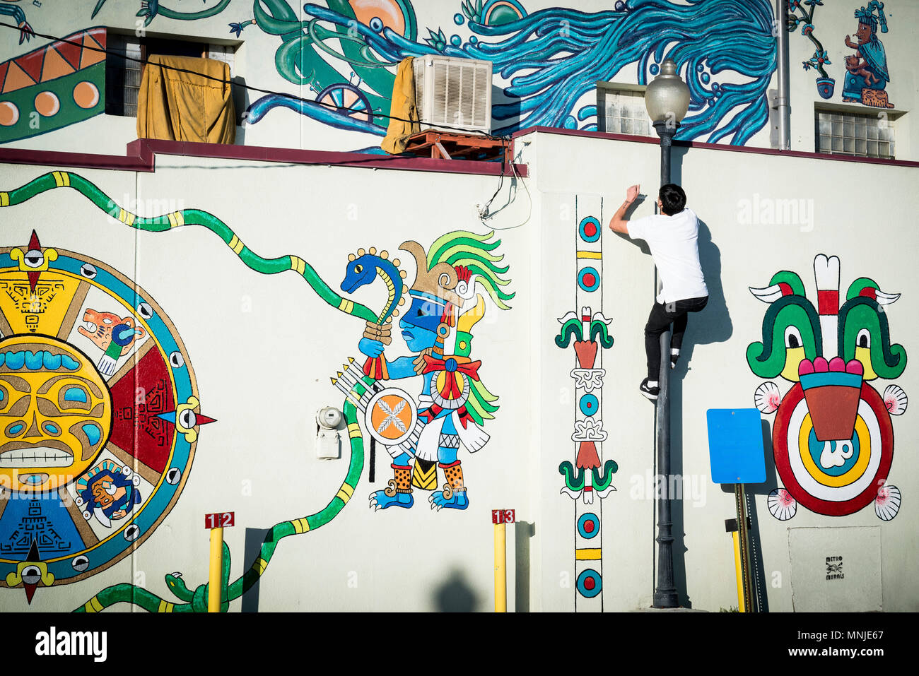 Young parkour athlete climbing up wall covered in street art in Denver, Colorado, USA - Stock Image
