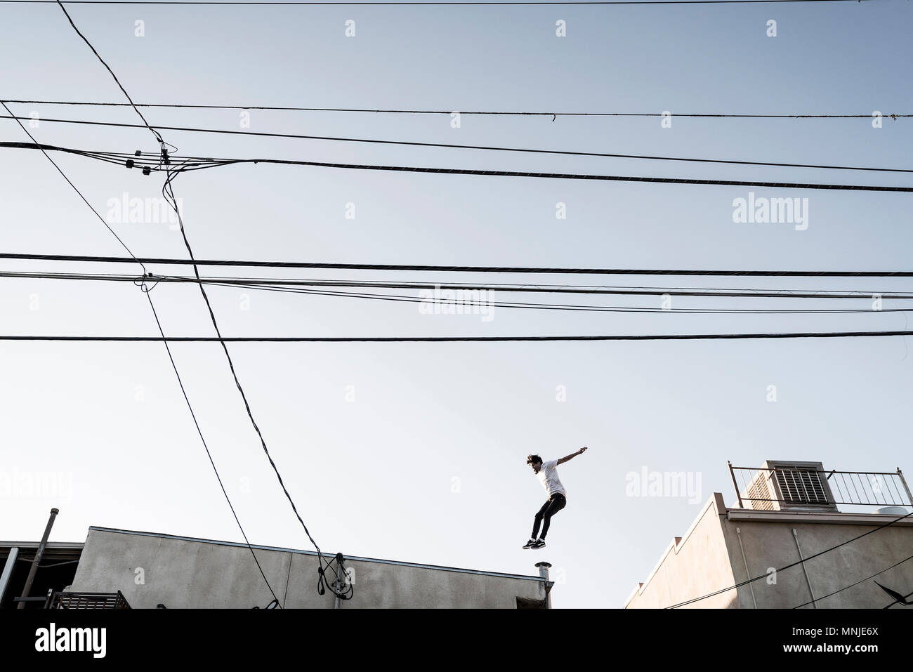 Side view of parkour athlete in mid-air while jumping between rooftops, Denver, Colorado, USA - Stock Image