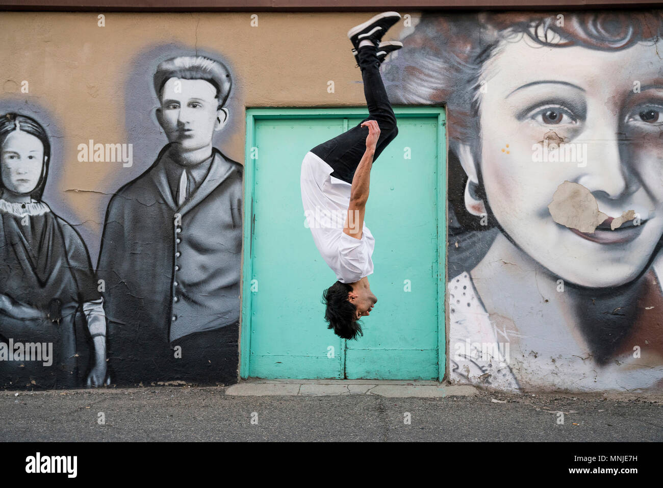Young fit parkour athlete doing backflip in front of street art, Santa Fe Arts District, Denver, Colorado, USA - Stock Image