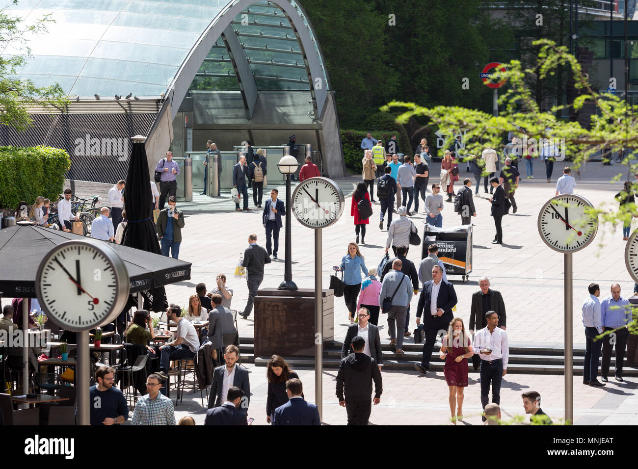 Canary Wharf, clocks show the time just before 12pm outside the underground station with employees milling around enjoying the sunshine - Stock Image