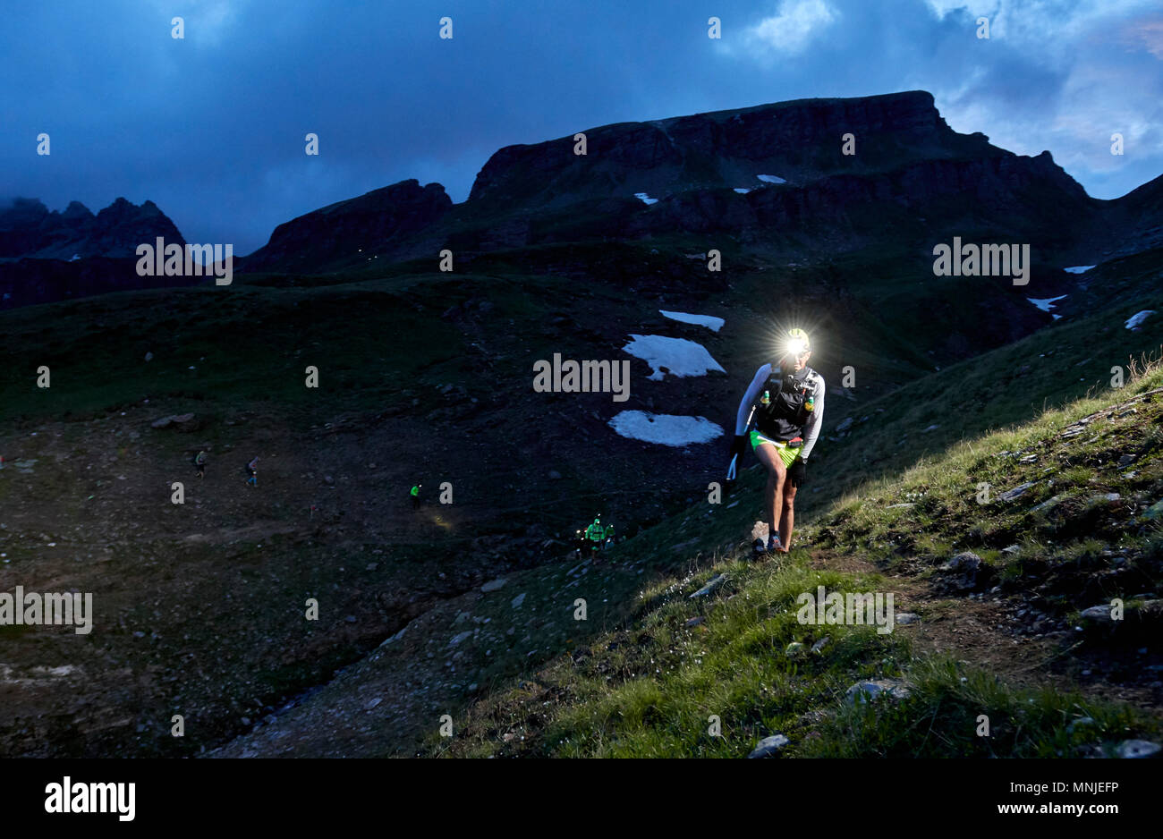 Hikers with headlamps hiking at evening, Alpe Devero, Verbania, Italy - Stock Image