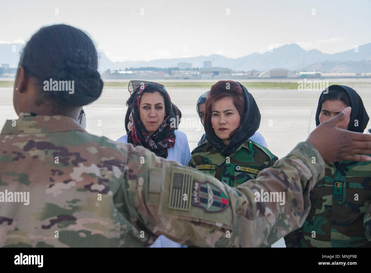 Afghan Air Force medics listen to Master Sgt. Ruth Celestine, Train, Advise, Assist Command-Air medical advisor, as she talks about the importance of casualty evacuation procedures with Afghan Air Force medics, March 3, 2018, Kabul Air Wing, Afghanistan. For many of the medics the information provided with the training was new. - Stock Image