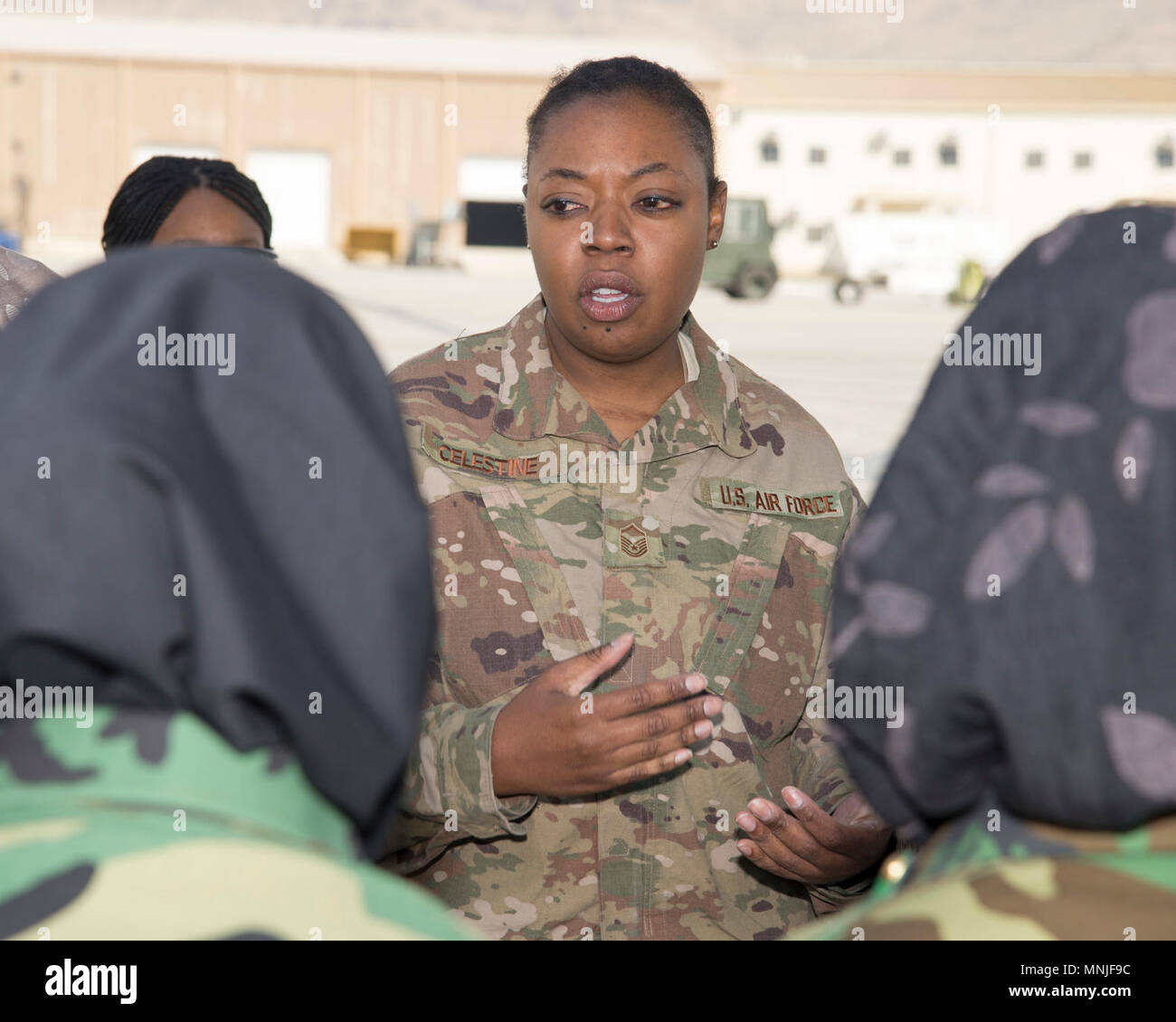 Master Sgt. Ruth Celestine, Train, Advise, Assist Command-Air medical advisor, talks about casualty evacuation procedures with Afghan Air Force medics, March 3, 2018, Kabul Air Wing, Afghanistan. Celestine coordinated this training as an overview of the process to help the Afghans understand how to load and unload patent litters onto a C-130. - Stock Image