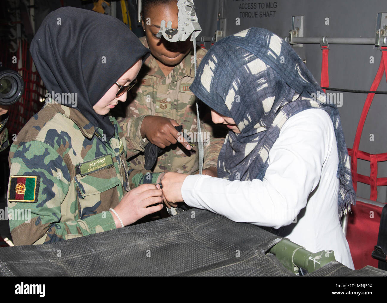 Master Sgt. Ruth Celestine, Train, Advise, Assist Command-Air medical advisor, talks to Afghan Air Force medics informing them about how to lock a patient littler in place during a C-130 casualty evacuation orientation March 3, 2018, Kabul Air Wing, Afghanistan. Over all 24 medics participated in the training, some of which had never done training like this before. - Stock Image