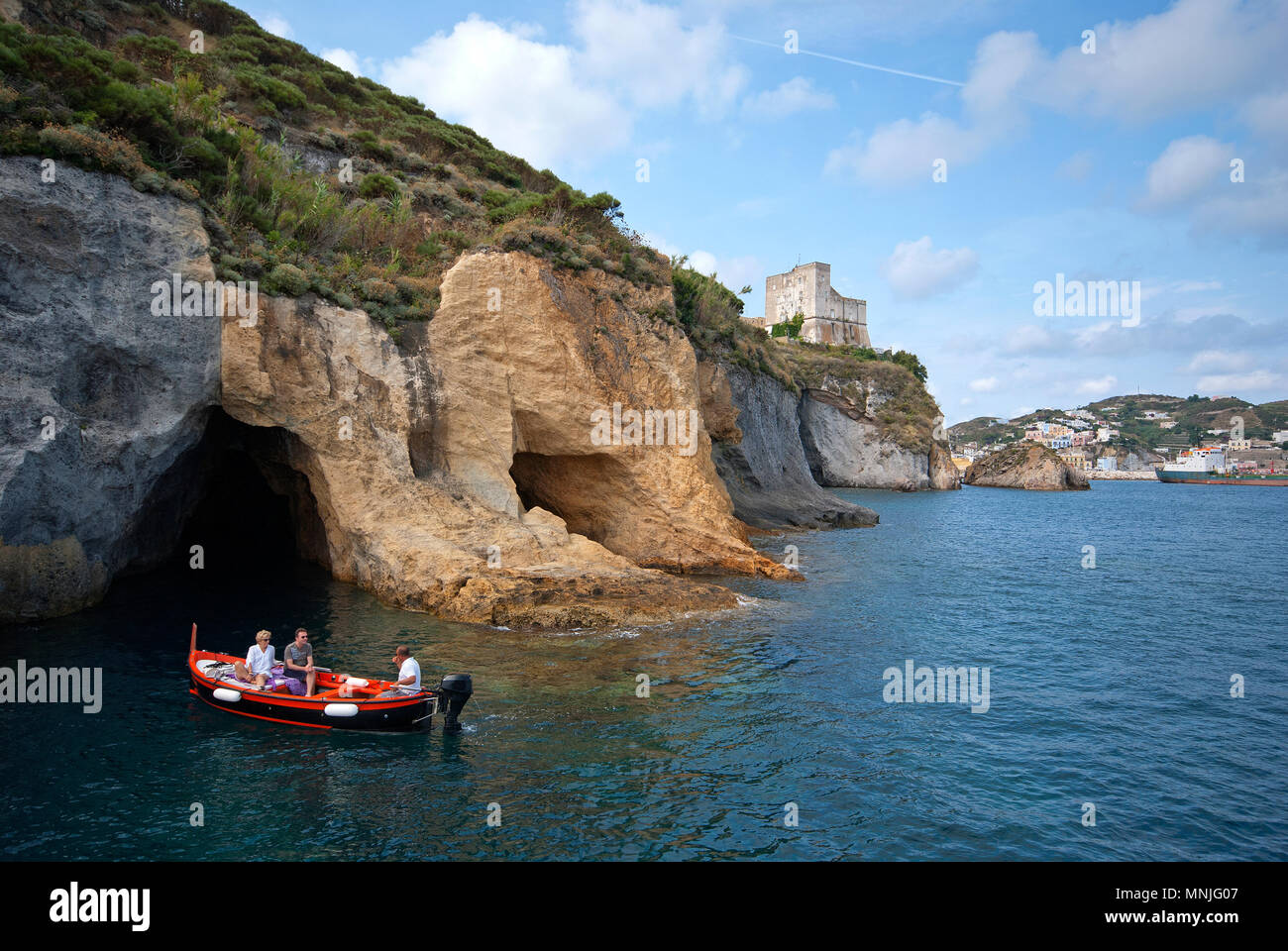 Guided boat tour near caves at Ponza Island (clearly visible the Bourbons Tower), Lazio, Italy - Stock Image
