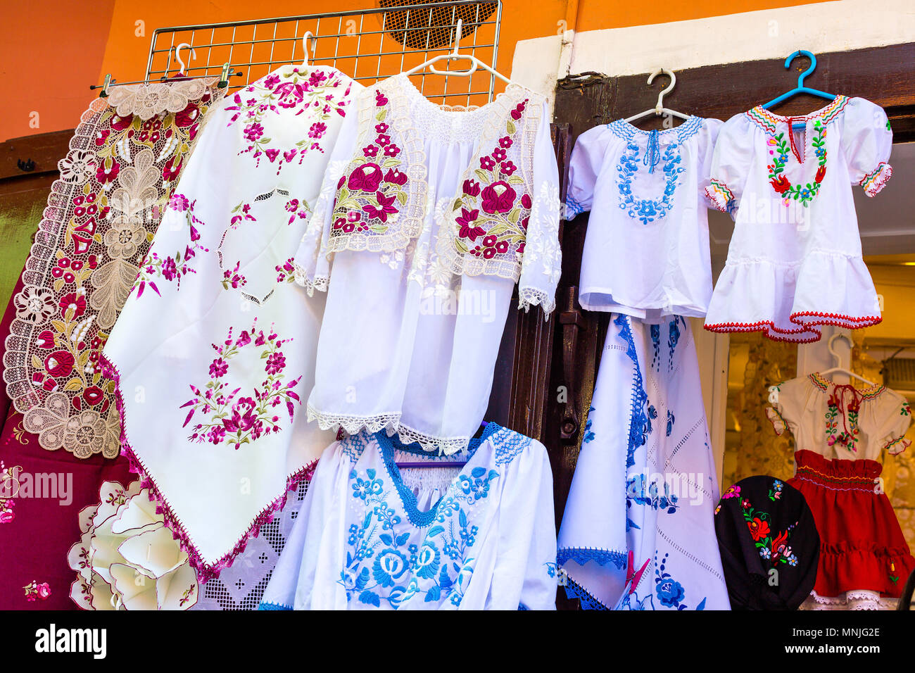 Beautiful bright ethnic shirts and tablecloths with traditional Hungarian embroidery in a street store - Stock Image