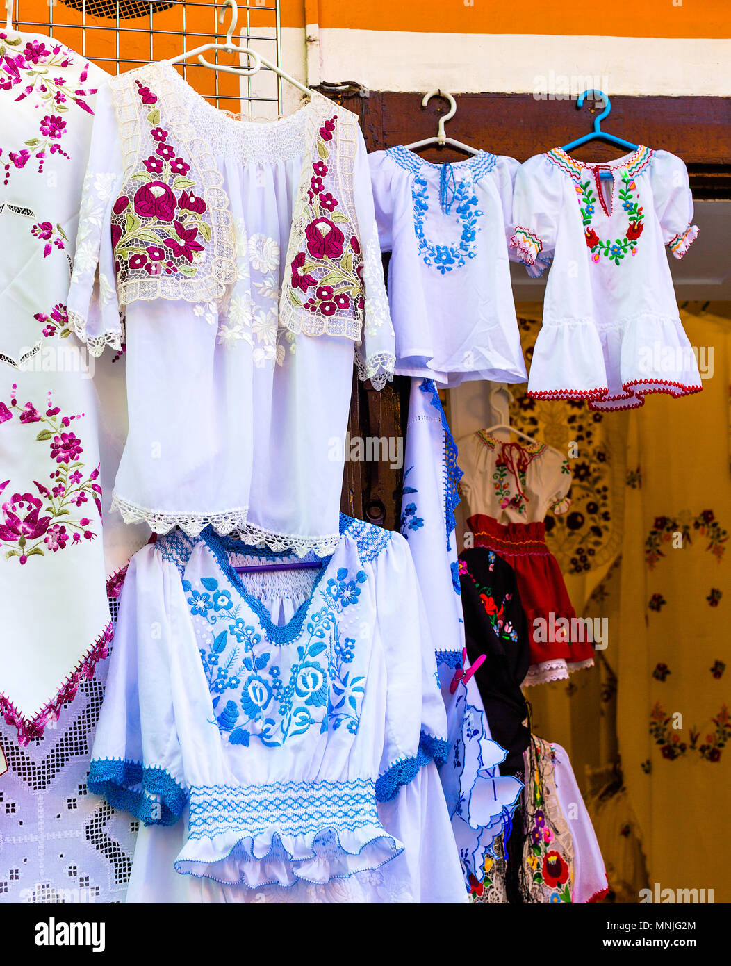Beautiful bright ethnic shirts and tablecloths with traditional Hungarian embroidery in a street store. Vertical photo - Stock Image