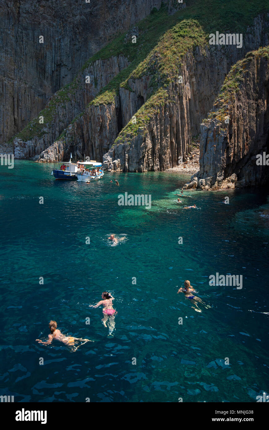 Swimming near the cliffs known as 'the cathedrals', Palmarola Island, Lazio, Italy - Stock Image