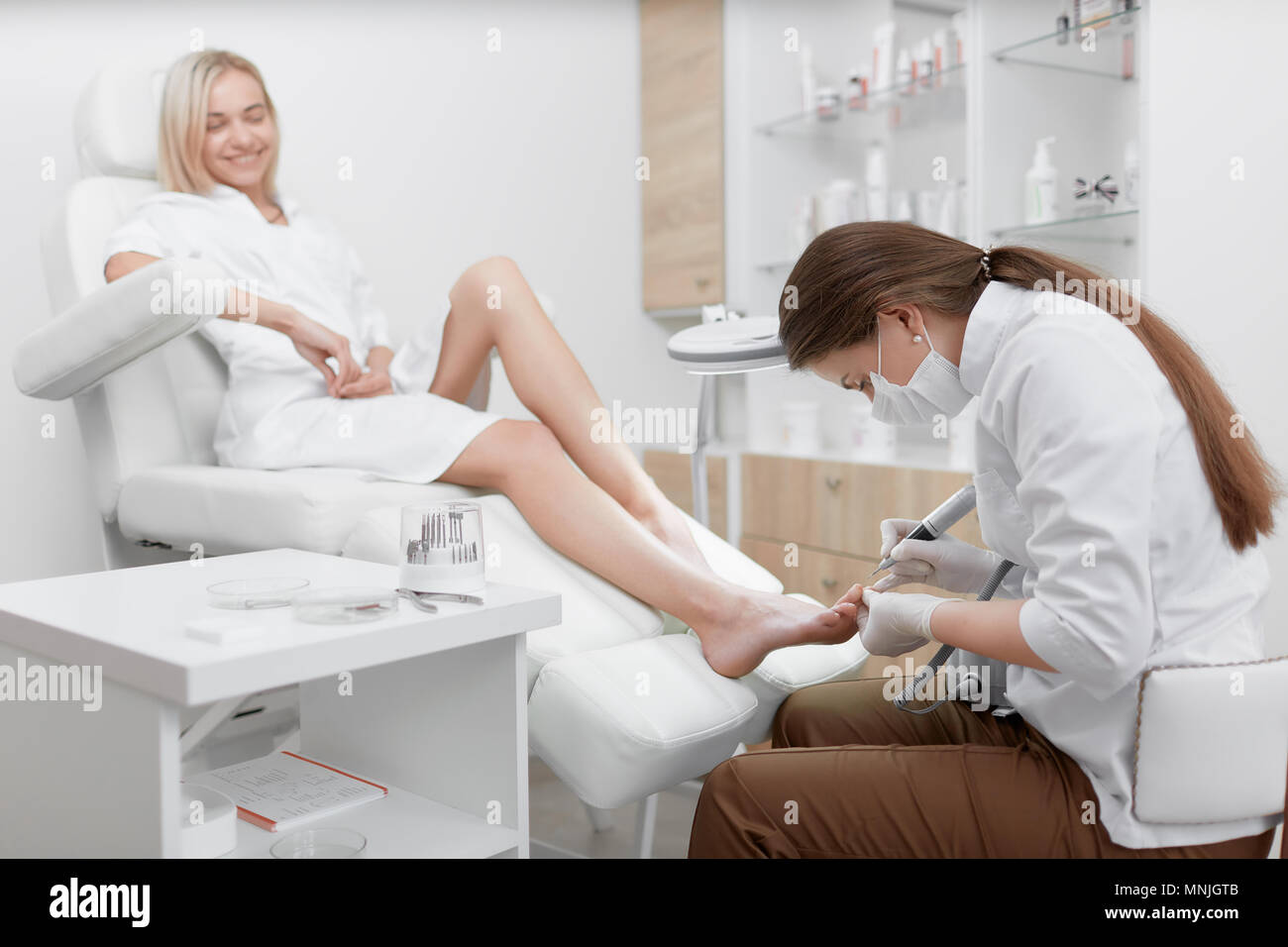 Podiatrist making procedure for smiling clients foot. - Stock Image