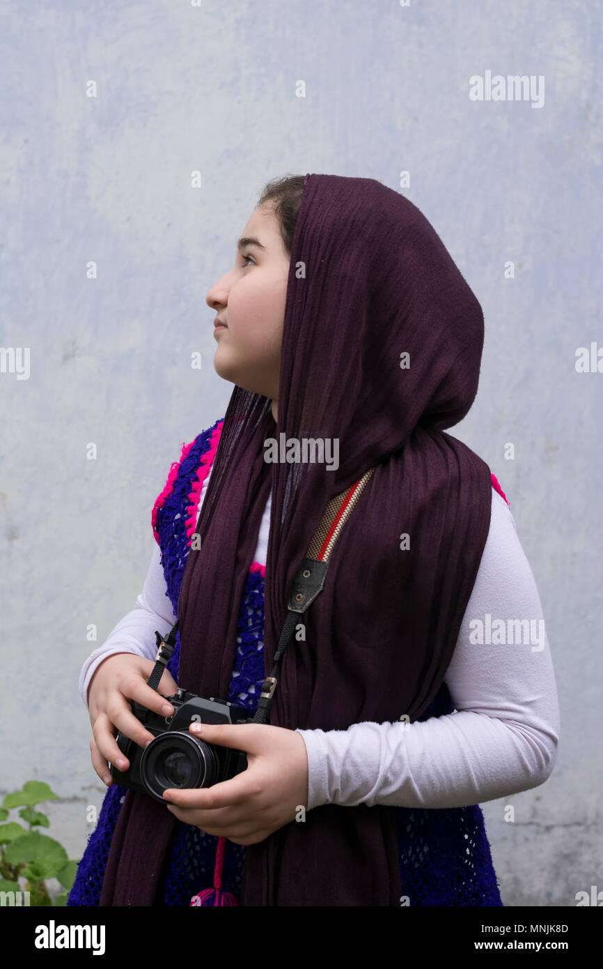 Beautiful Muslim girl looking for subjects to photograph by analogue camera - Stock Image