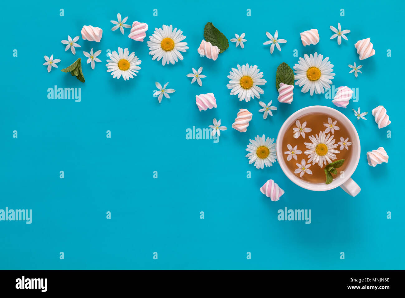 Cup of tea with marshmallows and flowers blossom  bouquets on blue surface. Flat lay, top view sweet food floral background. - Stock Image