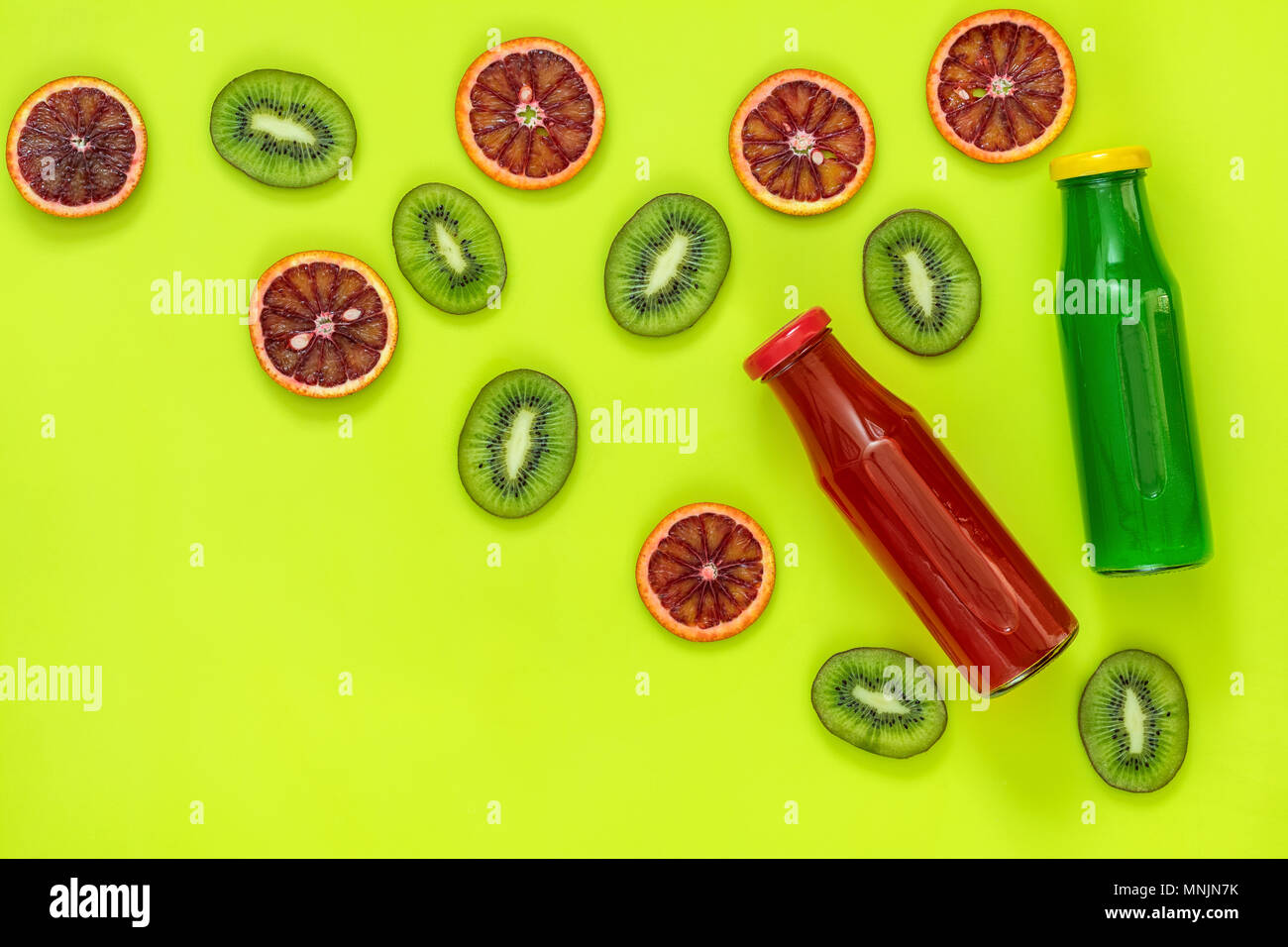 Beautiful food art background.  Green and red juice in glass bottles sliced kiwi and blood orange fruit on bright green surface. - Stock Image