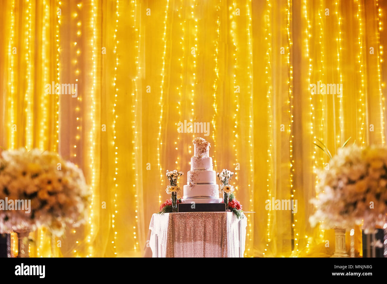 Beautiful Four Layers Wedding On The Table Stage Decoration With LED Light In Yellow Golden Theme Part Of Biuquet Flower Blurry Foreground