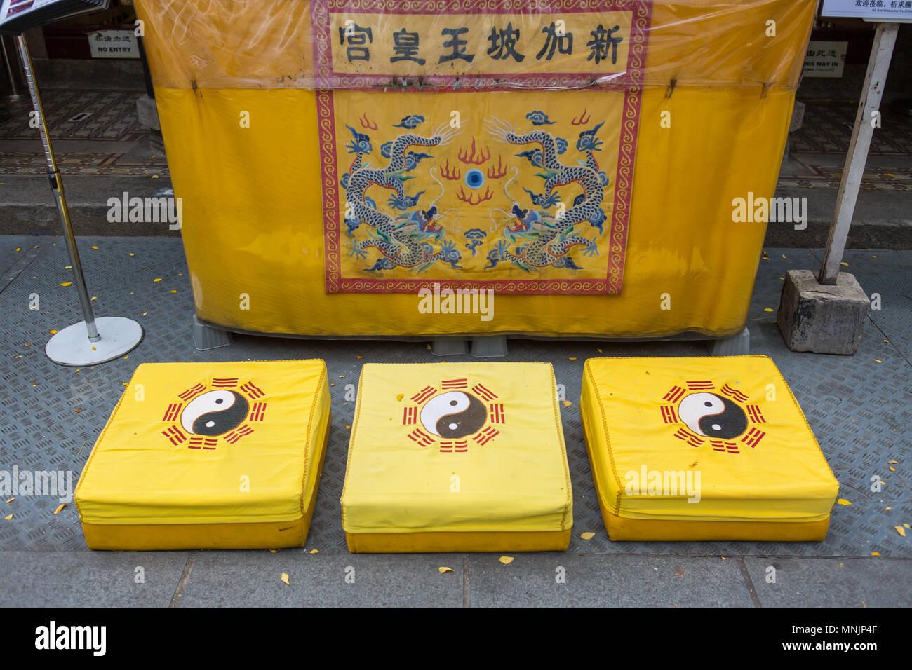 Three kneeling pad outside a Taoist temple. - Stock Image