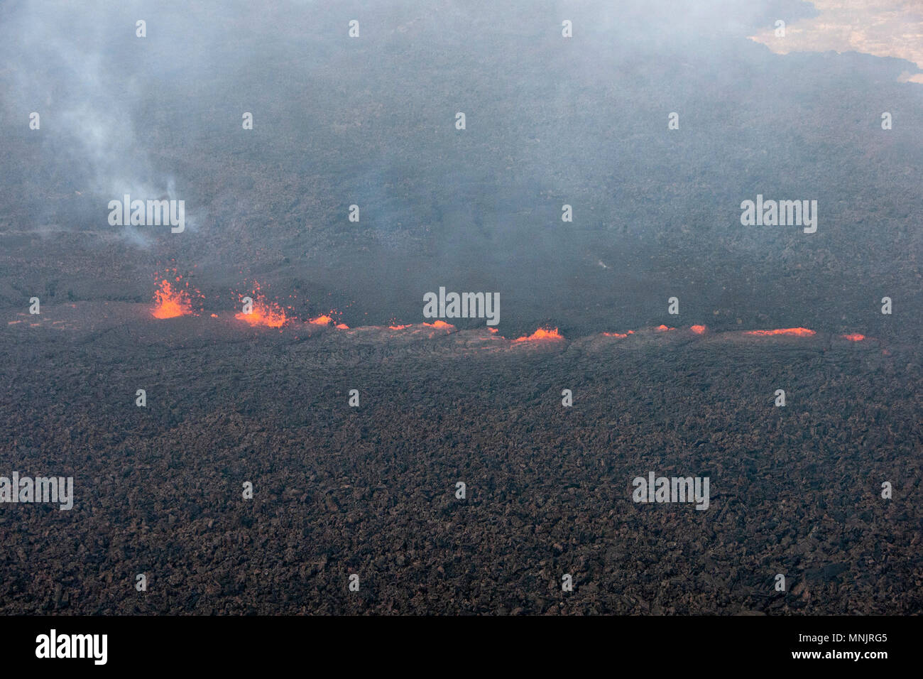 Lava and poison gases bubble out from a fissure caused by the eruption of the Kilauea volcano at Leilani Estates May 17, 2018 in Pahoa, Hawaii. The recent eruption continues destroying homes, forcing evacuations and spewing lava and poison gas on the Big Island of Hawaii. - Stock Image