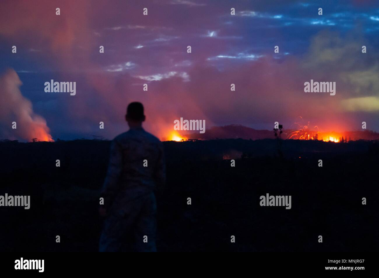 A Hawaii Air National Guard Airman observes three volcanic fissures spewing lava and poison gas into the evening sky from the eruption of the Kilauea volcano May 15, 2018 in Pahoa, Hawaii. The recent eruption continues destroying homes, forcing evacuations and spewing lava and poison gas on the Big Island of Hawaii. - Stock Image