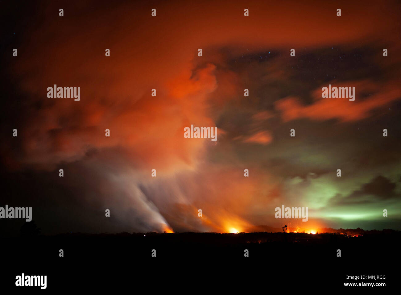 Lava explodes into the night sky from the 17th fissure caused by the eruption of the Kilauea volcano at Lanipuna Gardens May 15, 2018 in Pahoa, Hawaii. The recent eruption continues destroying homes, forcing evacuations and spewing lava and poison gas on the Big Island of Hawaii. - Stock Image