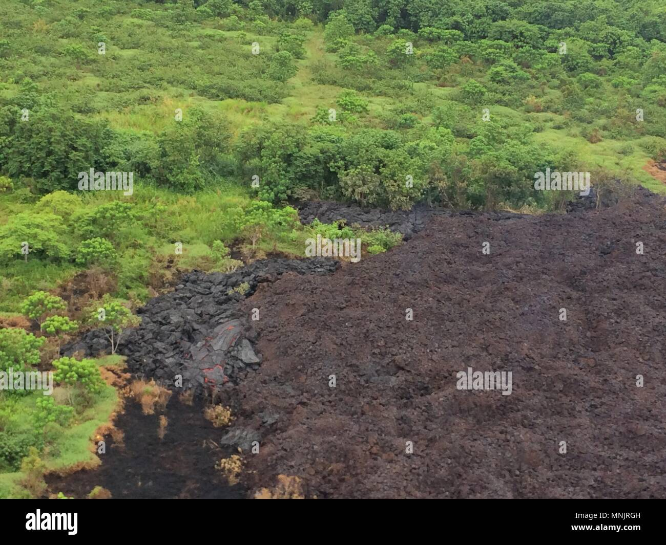 Lava flow from fissure 17 in the east rift zone begins to slow as as it oozes out of the earth from the eruption of the Kilauea volcano May 17, 2018 in Pahoa, Hawaii. The recent eruption continues destroying homes, forcing evacuations and spewing lava and poison gas on the Big Island of Hawaii.Stock Photo