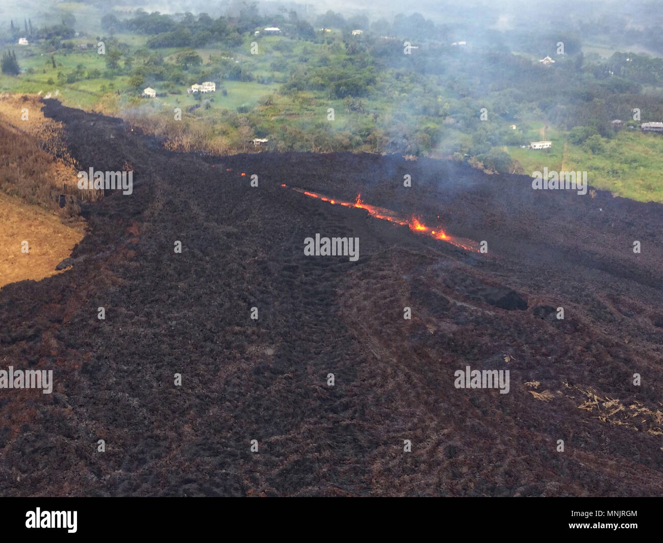 Lava and poisonous sulfur dioxide plumes rise from fissure 17 along the eastern rift caused by the eruption of the Kilauea volcano May 17, 2018 in Pahoa, Hawaii. The recent eruption continues destroying homes, forcing evacuations and spewing lava and poison gas on the Big Island of Hawaii.Stock Photo