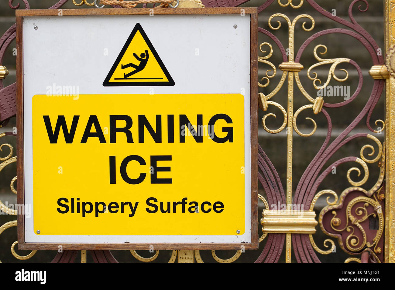 Warning ice slippery surface sign black text on yellow and white background with symbol of a man slipping on ice on ornate iron gates. Winter freezing - Stock Image