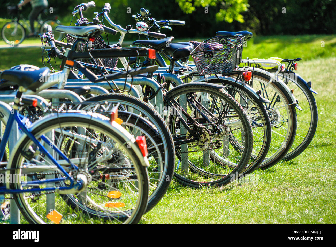 Wolfsburg, lower saxony, germany, May 5, 2018: Abstracted image with intentionally low depth of field from a group of bicycles parked on the lawn of a - Stock Image