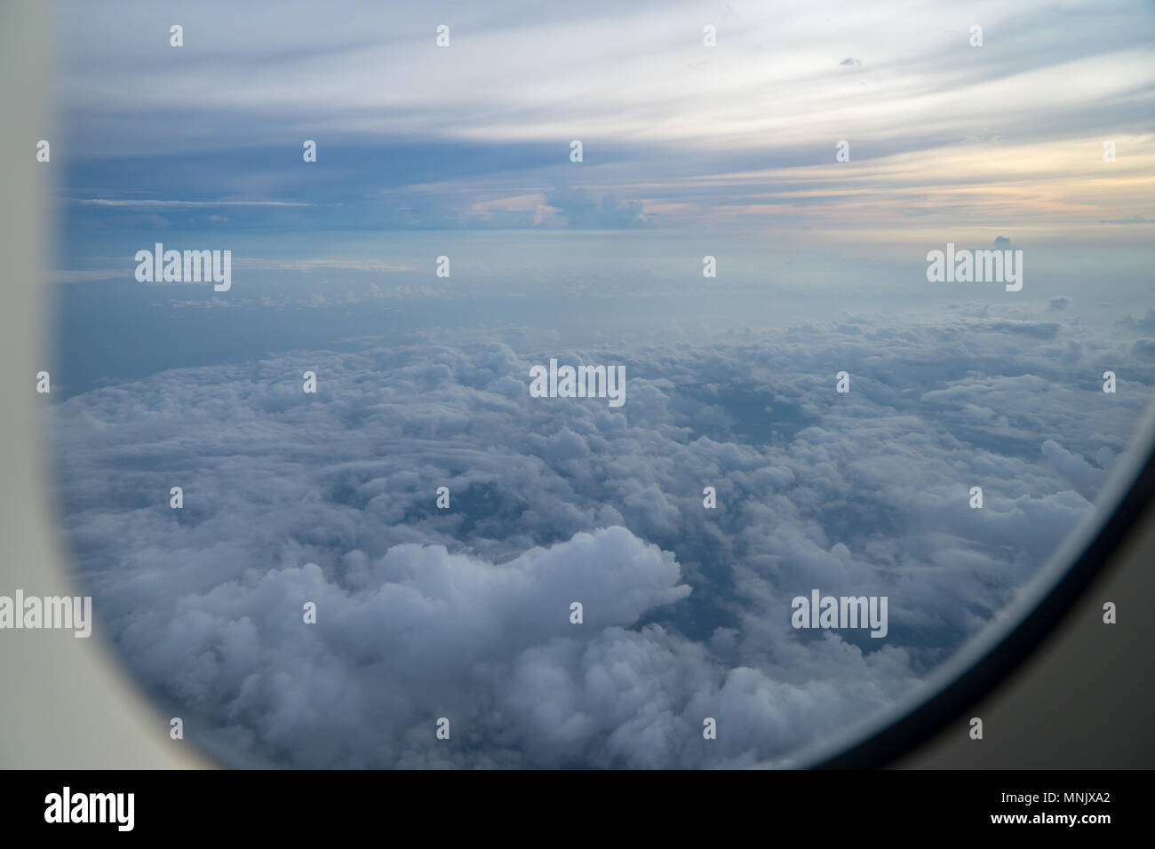 View out of airplane window with clouds at sunset. Stock Photo