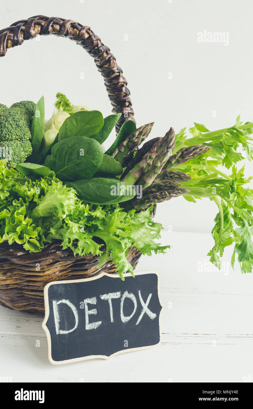 Detox concept with green vegetables in a basket: spinach, lettuce, asparagus, broccoli, fennel and celery. White wooden background. Clean eating Veget Stock Photo
