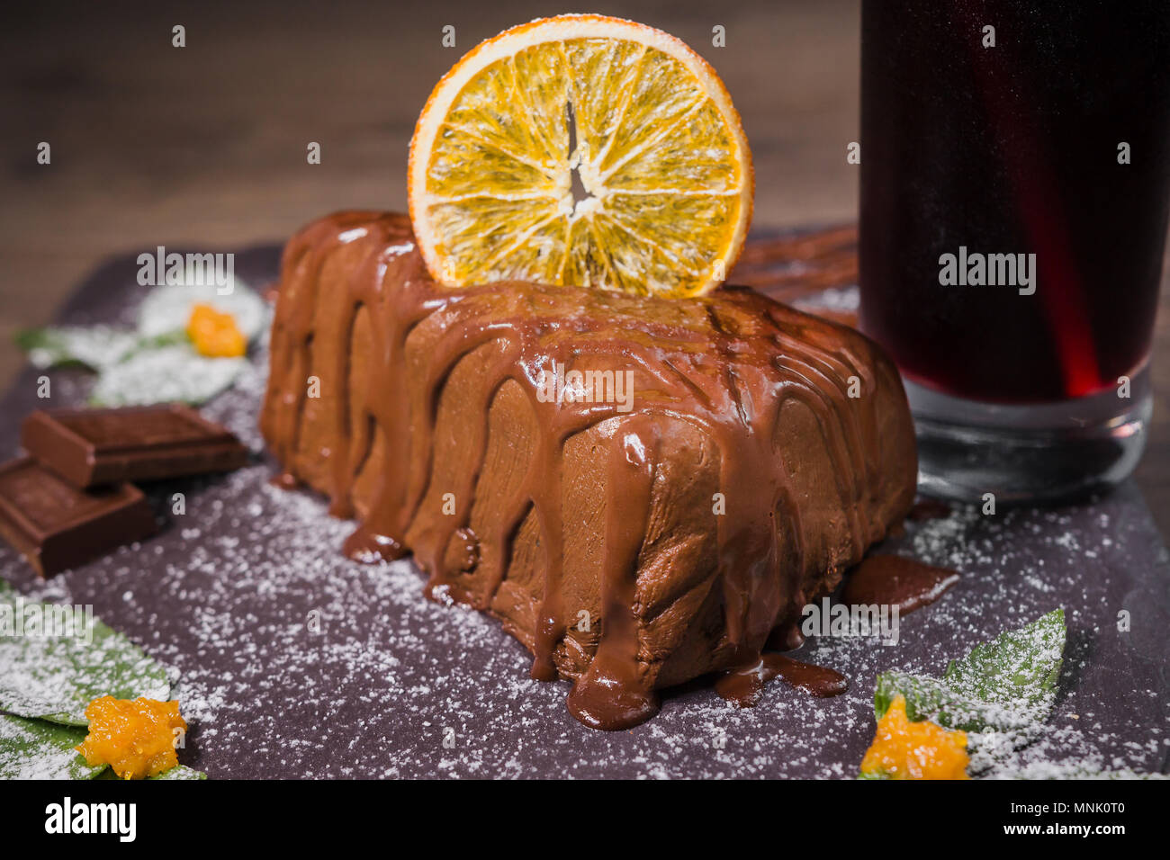 Chocolate dessert with orange chips on a wooden background - Stock Image