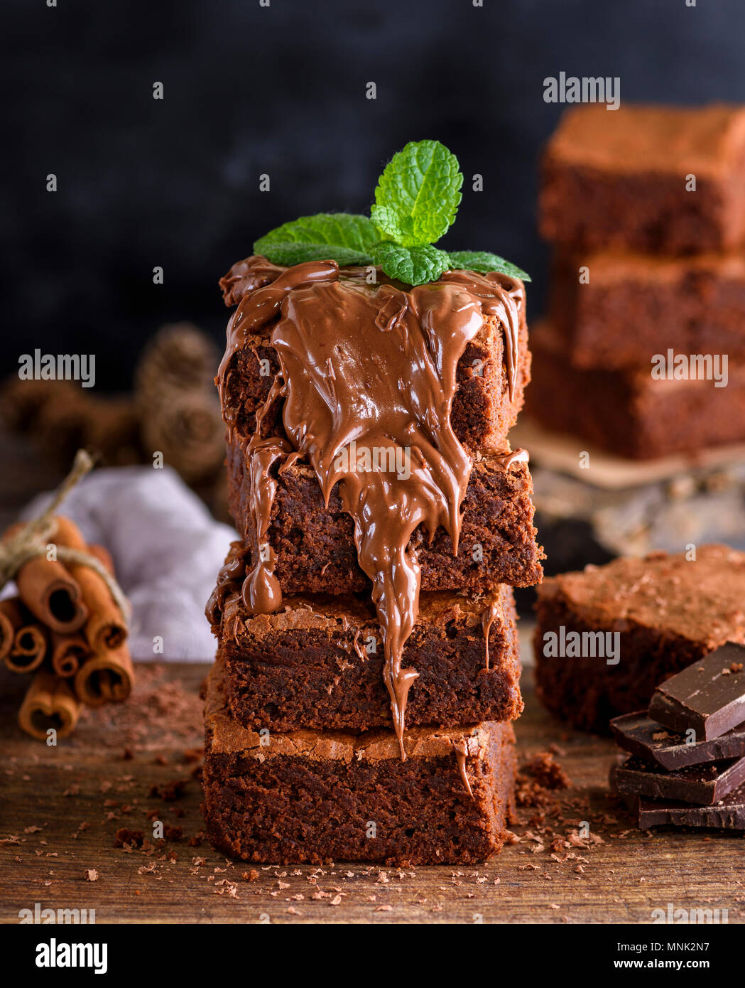 stack of square pieces of baked brownie chocolate poured on brown wooden board, close up - Stock Image