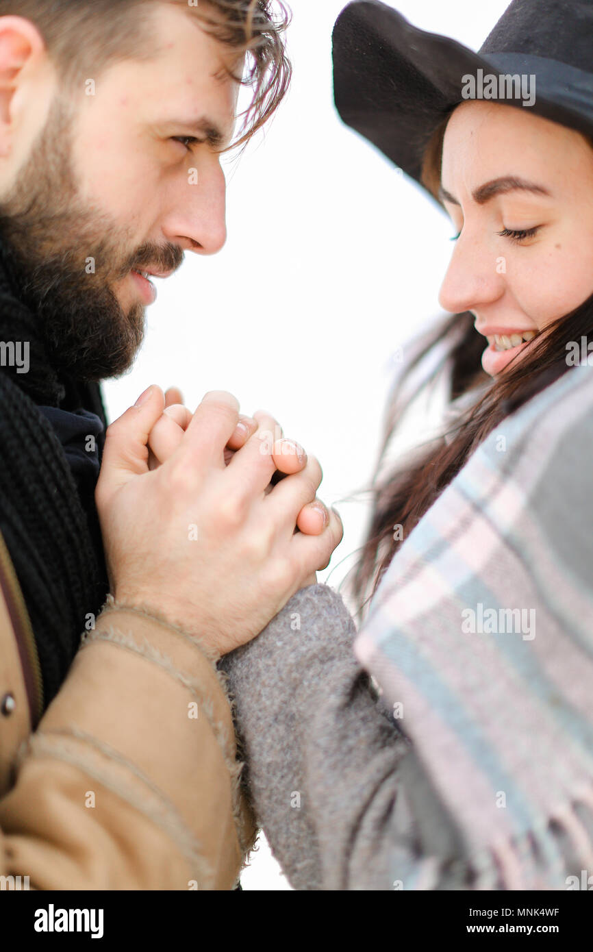 Portrait of american man holding woman hand in white background, wearing coat with scarf. - Stock Image