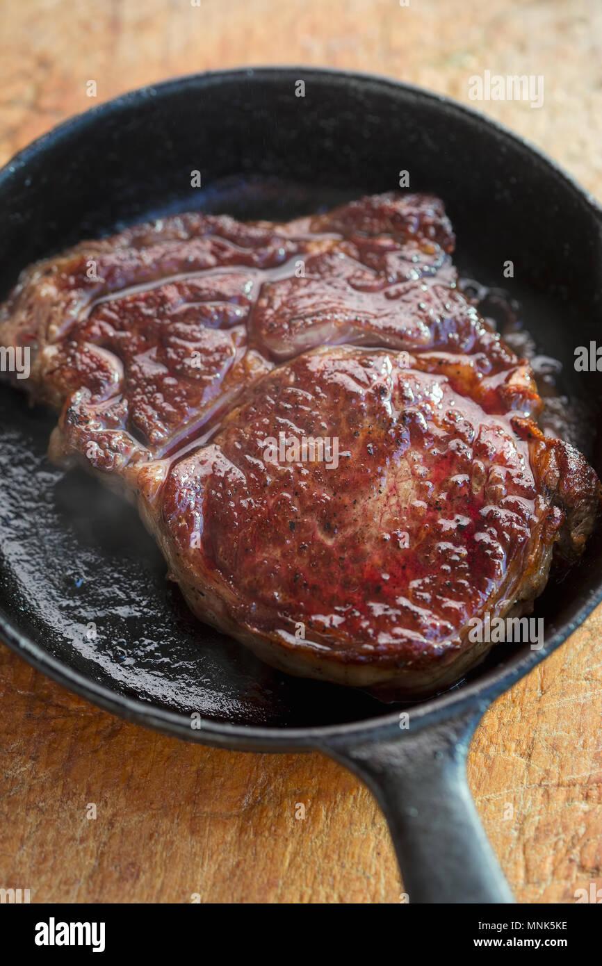 Rib eye steak fried on vegetable oil on iron cast - Stock Image